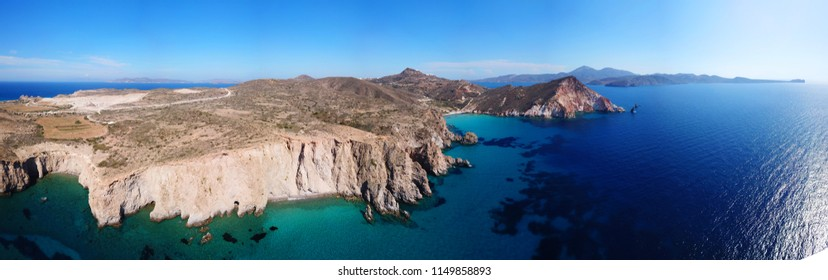 Aerial drone bird's eye view ultra wide panoramic photo of iconic volcanic turquoise clear water beach of Plathiena, Milos island, Cyclades, Greece