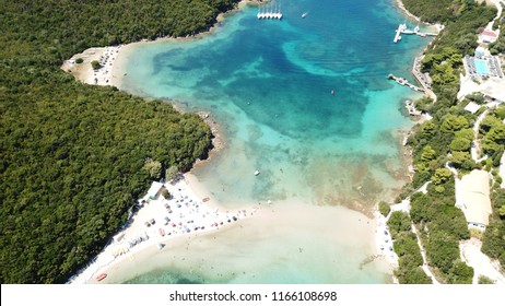 Aerial drone bird's eye view photo of popular and iconic turquoise beach of Bella Vraka in island of Mourtemeno with sunbeds and canoes forming a blue lagoon, Sivota bay, Epirus, Greece