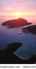 Aerial drone bird's eye view photo of iconic turquoise bay of Sivota forming a blue lagoon with beautiful colours and clouds at sunset, Epirus, Greece