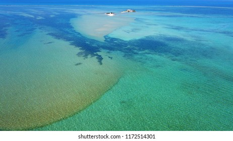 Aerial drone bird's eye view photo of tropical and exotic coral reef forming an atoll archipelago with beautiful sapphire and turquoise open ocean