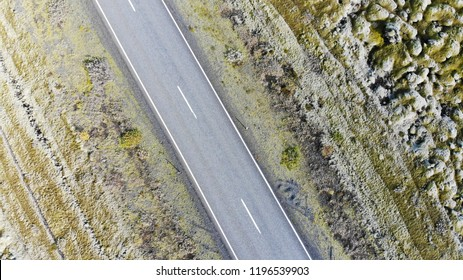 Aerial drone birds eye view of a street crossing a rugged landscape in Iceland