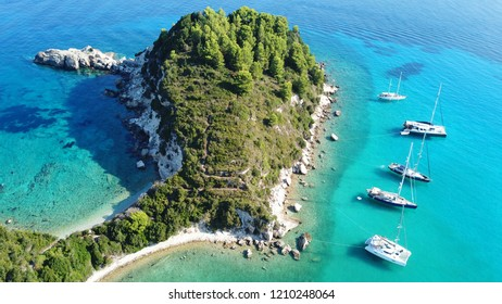 Aerial drone bird's eye view photo of sail boat docked in tropical caribbean paradise bay with white rock caves and turquoise clear sea