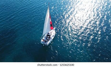 Aerial drone bird's eye view photo of small sail boat cruising in mediterranean open deep blue sea