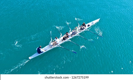 Aerial drone bird's eye view of sport canoe operated by team of young men in deep blue sea