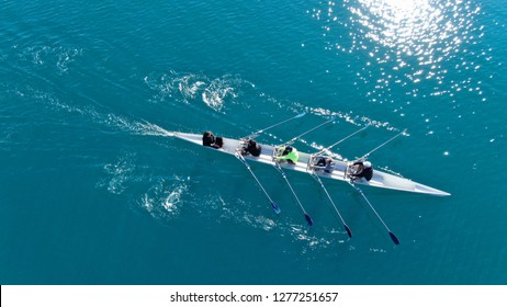 Aerial drone bird's eye view of sport canoe operated by team of young men in emerald clear sea