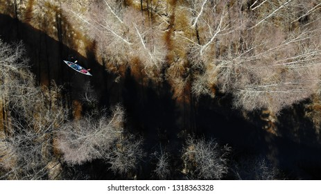 Aerial drone bird's eye view of two hikers who paddle a canoe in dark water river in wilderness