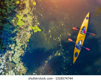 Aerial drone bird's eye view photo of two kids enjoying kayak ride on beautiful river. Little boy and teenager girl kayaking on hot summer day. Water sport fun. Canoe and boat for children