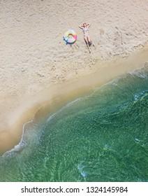 Aerial drone bird's eye view of Beautiful girl having fun on the sunny tropical beach
