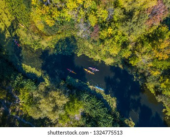 Aerial drone bird's eye view photo of Happy family with two kids enjoying kayak ride on beautiful river. Little boy and teenager girl with their parents kayaking on hot summer day. Water sport fun