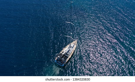 Aerial drone bird's eye view photo of small sail boat cruising in mediterranean open deep blue sea