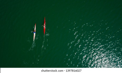 Aerial drone bird's eye view of sport canoe operated by team of young men in green sea waters. Aerial view of rowing team in Muğla / Turkey - 05.07.2019