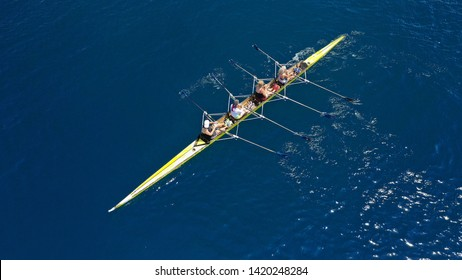 Aerial drone bird's eye view of yellow sport canoe operated by team of young women in deep blue sea waters