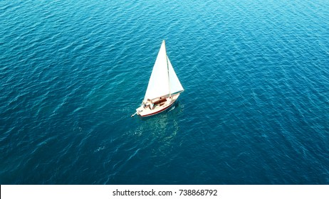 Aerial drone, bird's eye view of yacht cruising in tropical turquoise and sapphire sea
