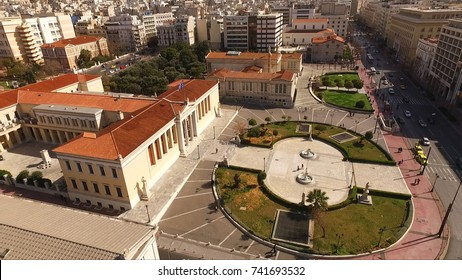Aerial drone bird's eye view of iconic neoclassic University of Athens with beautiful scattered clouds, Athens historic center, Attica, Greece