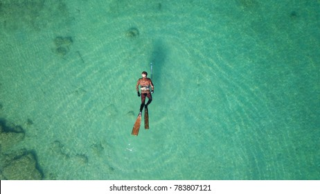Aerial drone bird's eye view photo of diver swimming in turquoise clear tropical waters