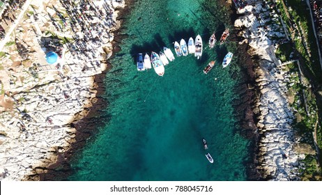 Aerial drone bird's eye view of turquoise clear waters seascape located in a Greek island with traditional fishing boats docked and small picturesque chapel