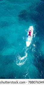 Aerial drone bird's eye view of man exercising sup board in turquoise tropical clear waters