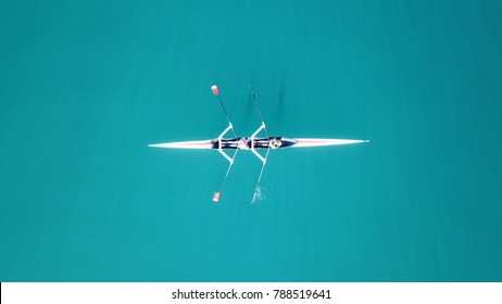 Aerial drone bird's eye view of sport canoe operated by 2 young women in turquoise clear waters