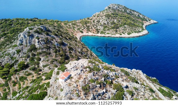Aerial drone bird's eye view from small islet of Dorousa with small chapel on top, Aponisos, Agistri island, Saronic gulf, Greece