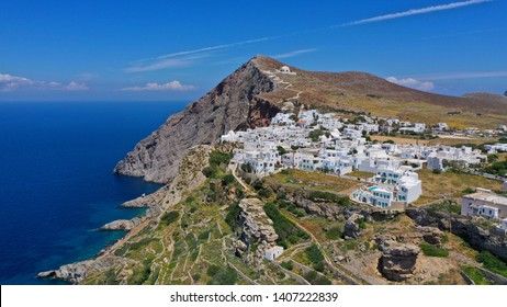 Aerial drone distant photo of picturesque village (chora) of Folegandros island featuring uphill church of Panagia (Virgin Mary) on top of steep hill overlooking the Aegean blue sea, Cyclades, Greece