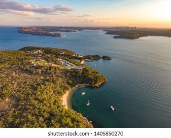 Aerial drone evening view of the Quarantine Station, part of Sydney Harbour National Park. Store Beach in foreground. Sydney harbour with North Head & South Head and city skyline in background.