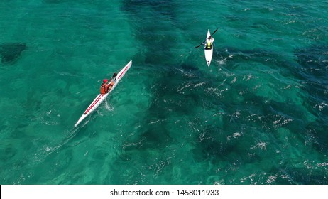 Aerial drone of fit man practising sport canoe in tropical crystal clear Mediterranean emerald sea