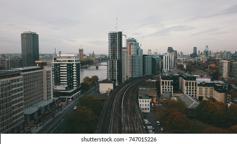 Aerial drone flight over clapham junction, between two condo buildings and then over the thames river towards london parliament and the