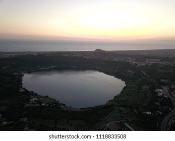 Aerial drone flight over a volcanic crater lake, Lake Avernus (Lago d'Averno) in the south of Italy near Pozzuoli and Napoli.  It was considered the entrance to Hades in roman mythology.