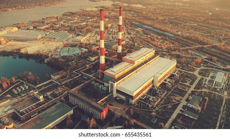 Aerial Drone Flight Photo of city main Power plant with two factory chimneys. Electricity station supply near Dnipro river. Industrial sunset cityscape. Kiev, Ukraine. Top view. Vintage filter toning