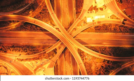 Aerial drone high speed night photo of urban elevated road junction and interchange overpass in city with light traffic