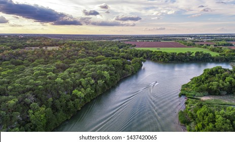An aerial drone image of a boat as it floats down the Brazos River in Waco, Texas.