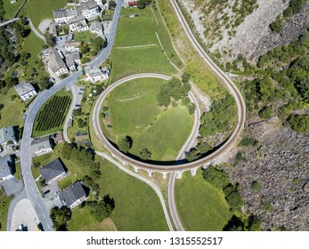 Aerial drone image of the Brusio spiral viaduct - a single-track nine-arched stone spiral railway viaduct, which is a unesco heritage of the Albula railway line in Switezrland