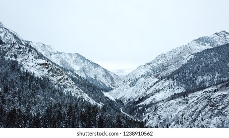 Aerial drone image of Cottonwod Canyon in Salt Lake City, Utah. Snow covered mountains and tress, protruding rocks with gray skies