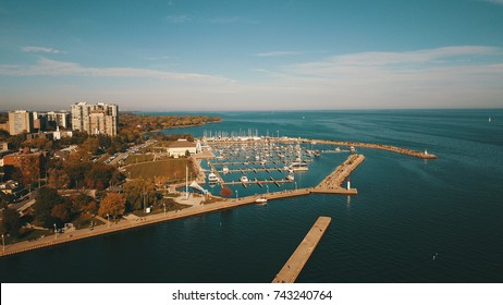 Aerial drone image of a flight over a harbor with bridges and tall buildings during autumn.