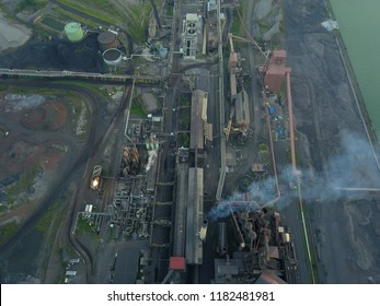 Aerial drone image of a large steel plant with billowing smoke stacks and an industrial wasteland.