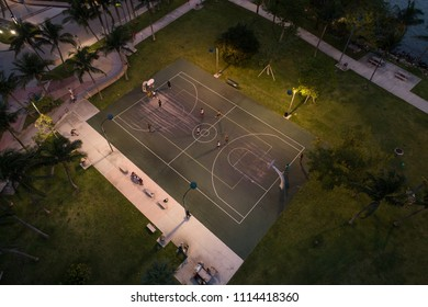 Aerial drone image of people playing basketball in  the city courts at night