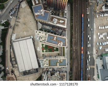 Aerial drone image of railroad tracks in a city with tall high rise tower buildings.