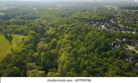 Aerial drone image of suburbs (urban sprawl) cutting into forest in Southern Ontario, Canada.