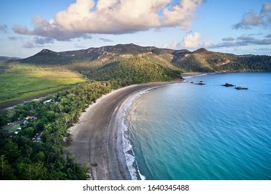 Aerial drone image at sunrise over Cape Hillsborough with blue water and green rainforest and nice morning warm sunlight