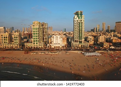 Aerial drone image of Tel Aviv, Israel waterfront at golden hour, featuring the Banana Beach and Royal Beach Hotel.