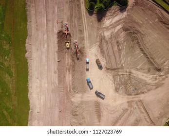 Aerial drone image (top view) of a construction site.  Heavy equipment is grading the land, moving and flattening out red clay soil.