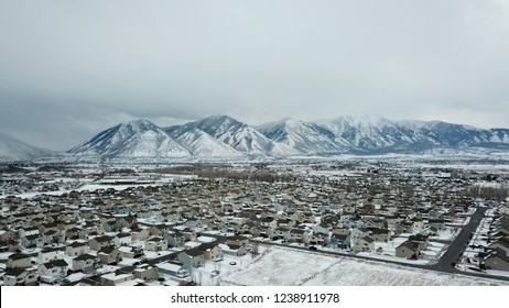 Aerial drone images of Provo Utah, Utah Valley. Snow covered neighborhoods with snow capped mountains in the back ground