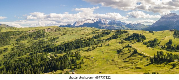 Aerial drone landscape of the meadows at high altitudes, forming gentle hills. Marmolada in the background. Dolomites, Alta Badia, Sud Tirol, Italy