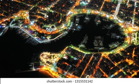 Aerial drone night shot of dazzling illuminated safe port of Marina Zeas with luxury yachts and sailboats docked in the heart of Piraeus, Attica, Greece