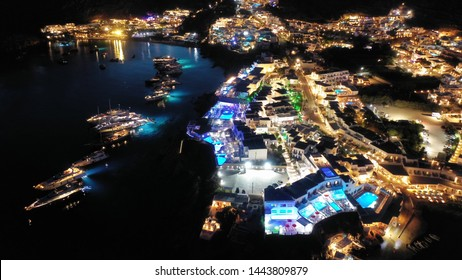 Aerial drone night shot of famous Psarou beach with luxury resorts and yachts docked, Mykonos island, Cyclades, Greece