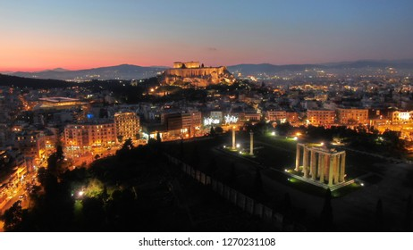 Aerial drone night shot of iconic Temple of Olympian Zeus and Acropolis hill at the background at dusk, Athens historic centre, Attica, Greece