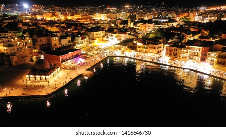 Aerial drone night shot of iconic and picturesque illuminated Venetian old port of Chania with famous landmark lighthouse and shops - restaurants serving Cretan traditional food, Crete island, Greece