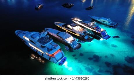 Aerial drone night shot of luxury yachts docked famous Psarou beach, Mykonos island, Cyclades, Greece