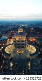 Aerial drone night view of Saint Peter's square in front of world's largest church - Papal Basilica of St. Peter's, Vatican -an elliptical esplanade created in the mid seventeenth century, Rome, Italy