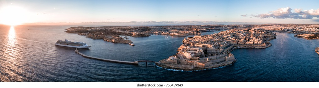 Aerial drone panorama sunrise photo- Cruise ship sailing into the Grand Harbour (harbor) of Valletta, Malta.  Island nation in the Mediterranean Sea, Europe.